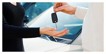 Ludzie przekazujący sobie kluczyki do samochodu