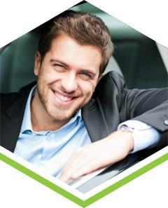 Uśmiechnięty, elegancko ubrany kierowca w samochodzie