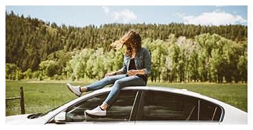 Kobieta siedząca na dachu jadącego samochodu